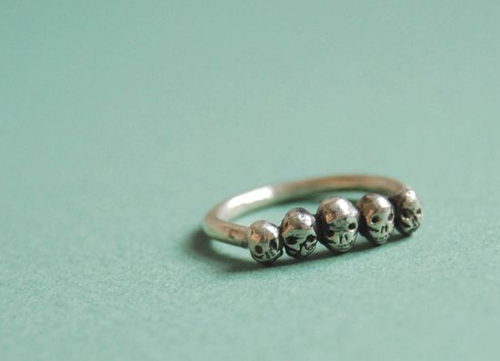 Row of tiny skulls sterling silver ring.