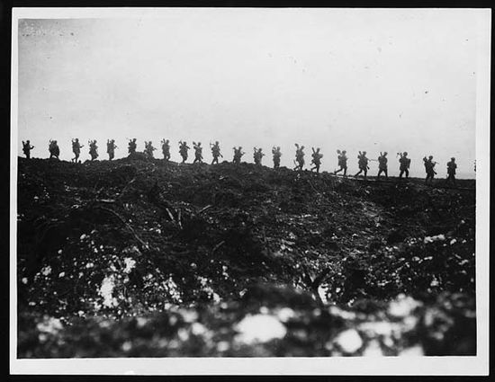 """Soldiers on the move at the Front, during World War I. """"Working parties going up to consolidate newly captured trenches"""". A line  of silhouetted soldiers are walking in single file across the top of a  small hill. Each man's pick or shovel can clearly be seen over his  shoulder. The ground is all churned up and covered with frost. National Library of Scotland via Flicker"""