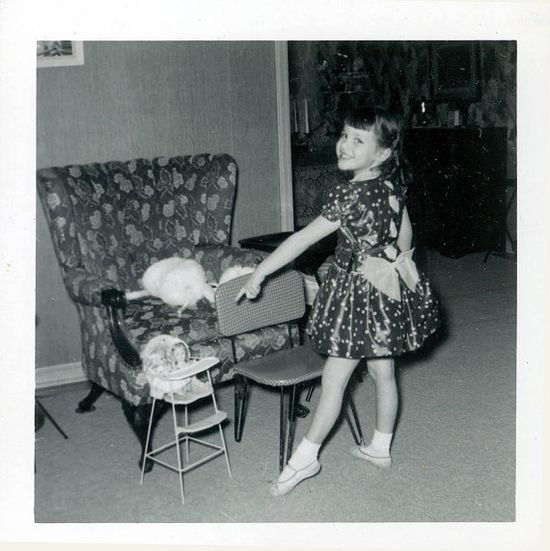 Vintage photo of little girl in ballet shoes playing with her dollies, circa 1950's.