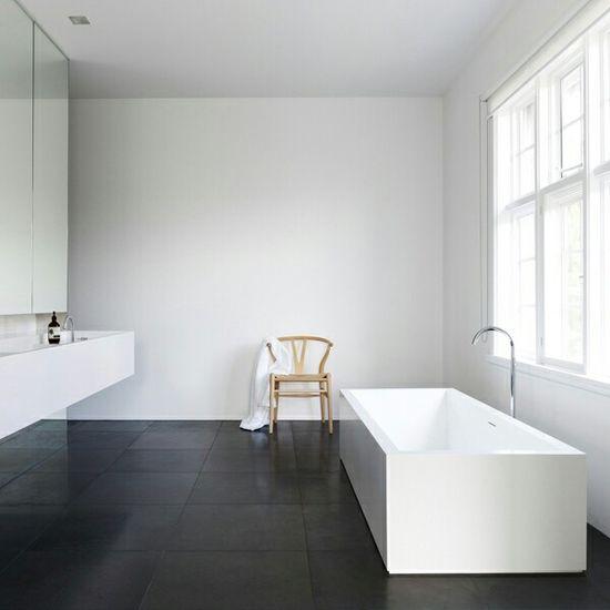 White bathroom with dark floor.