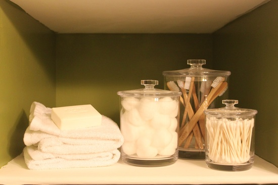 Bathroom Remodel.  Behr Grape Leaves.  Bathroom built in shelves.  Glass Canisters.  Guest toothbrushes.  Brown and green bathroom decor.  White handtowels.  Bathroom before and after remodel.