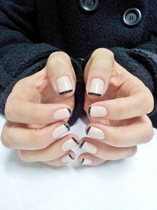 Nude nails with small black french tips.
