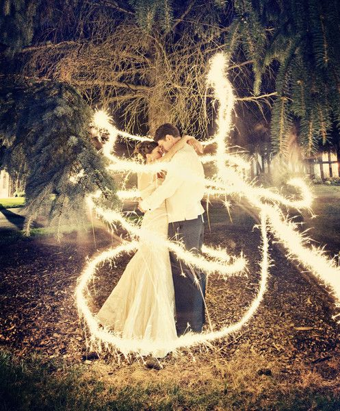 """""""DIY: Ask your photographer to do this! It's a long exposure shot with sparklers. All they had to do was stand there very still and someone else ran around them with a sparkler. It's like a fairy tale!""""   I would totally do this for one of my wedding photos"""