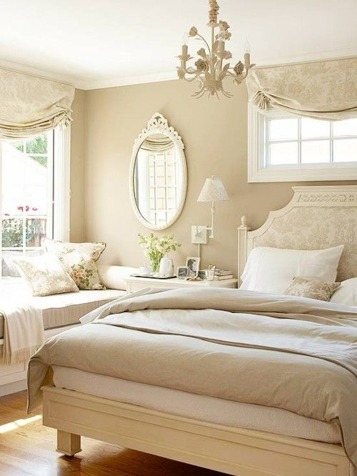 A beautiful example of a neutral-toned bedroom, with a damask headboard and a sunny window seat