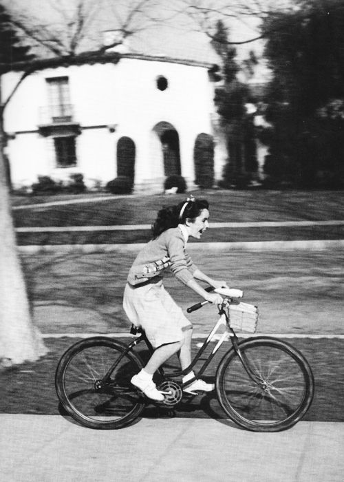 Elizabeth Taylor, age twelve, rides her bike through Beverly Hills in 1944. Photographed by Peter Stackpole.