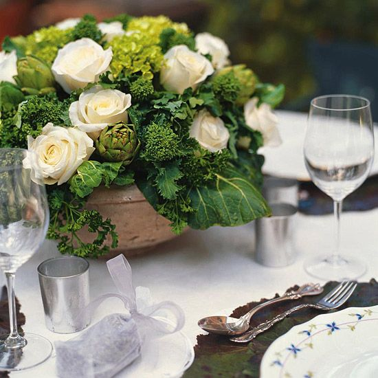 bowl arrangement with ivory roses, artichokes, broccoli and kale