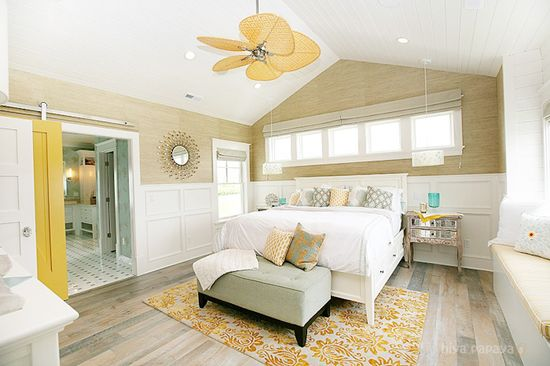 Master bedroom with paneling, grasscloth wallcovering, rustic wood floors, and sliding barn door to master bath.
