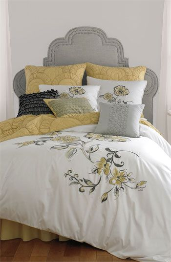 Gorgeous color palette of gray and yellow. Love the headboard and the gorgeous floral print.