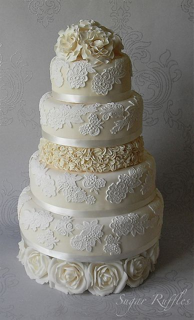 Lace wedding cake with ruffles and roses
