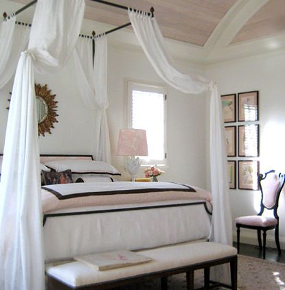 We love a four-post metal bed frame, draped in sheer white fabric!