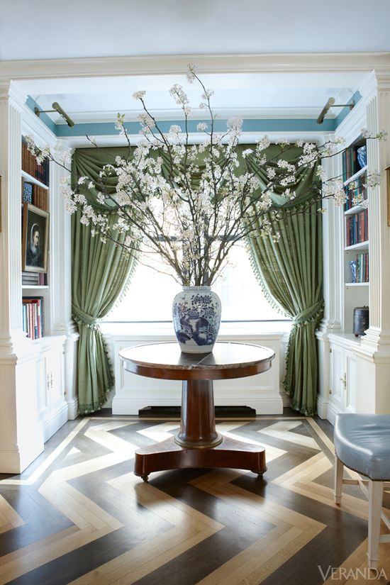 Chevron floors, library lights and bookshelves, blue paint, mossy green curtains, blue and white vase with cherry blossoms - Manhattan apartment designed by Nick Olsen.