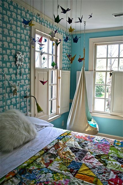 Turquoise walls, patchy quilt, hanging chair. This would be a great colour palette for an art space. I love the multi-colour paper cranes too!