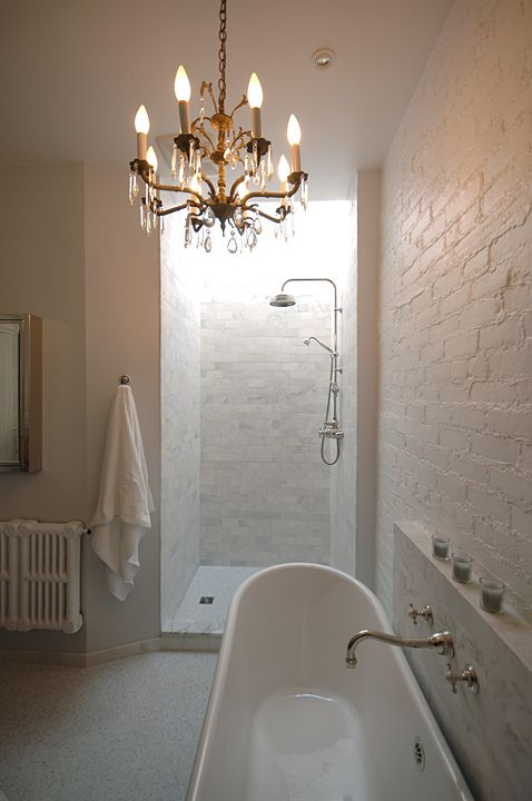 Gorgeous master bathroom design with white exposed brick wall, soaking tub, white carrara marble subway tiles shower surround, polished nickel wall-mount faucet, rain shower head and crystal chandelier.