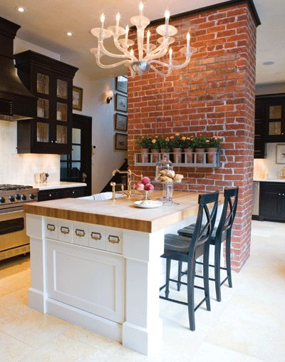 love the brick wall, the pretty chandelier and this amazing island with bar stools.