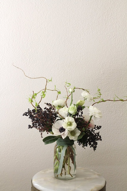 Privet and anemone arrangement by Sarah Winward. Love the structure of the twigs and the addition of ribbon around a simple glass jar. It's all in the detail.