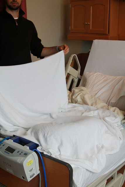 Photo set up for newborn photography is the hospital. Boppy on the bed with sheet held up in back