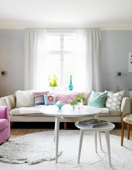 White couch, bright pillows, pink chair. ?