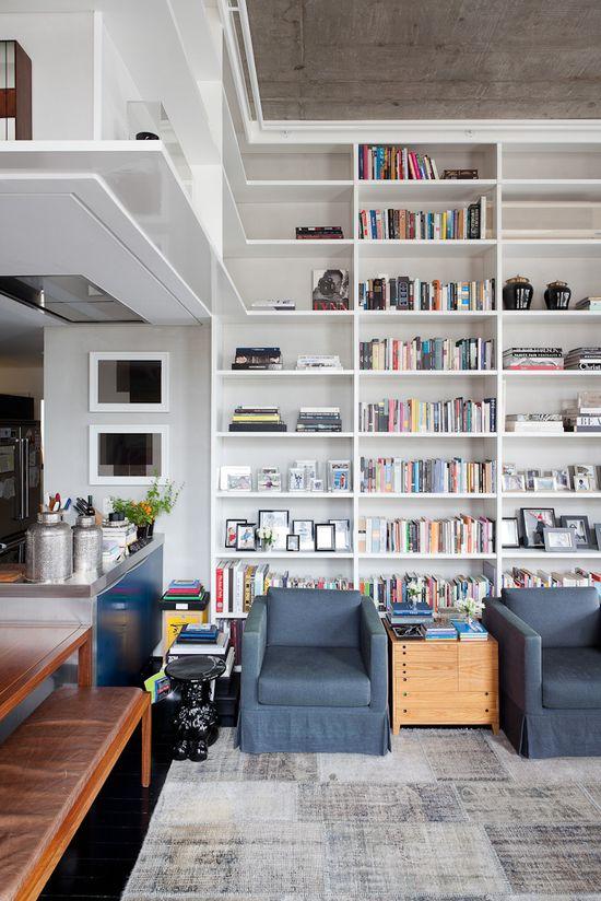 Loft in Itaim / FGMF Arquitetos Regal ist gleichzeitig Balustrade für Obergeschoss. Löst zwei Drei Probleme bzgl. Raumaufteilung.