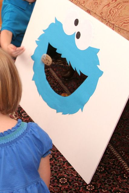 Throw the cookie in Cookie Monster's mouth game at a Cookie Monster Party #cookiemonster #partygames ~ Could be used as rainy day play. Great for eye /hand coordination. I love the graphic face of Cookie! (Wide Mouthed Frog activity instead?)