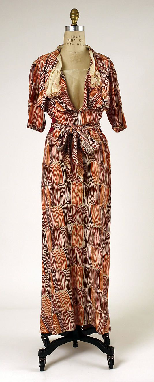 Haute Couture Charles Frederick Worth evening dress gown and long jacket coat ensemble from French 1930-1935 by designer Jean Charles Worth. #Historical #Costume made from silk in contrasting color and printed pattern with wool and metal buckle. Red long jacket coat and short sleeve, collar design in fitted bodice with tied sash belt at the waist and a long flowing dress underneath. #Vintage #Haute #Couture #Fashion House of Worth.