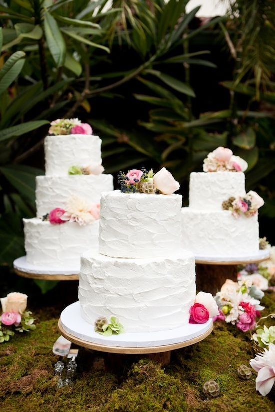 white wedding cakes placed on moss