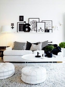 Gallery wall on a floating shelf + white pouf seating
