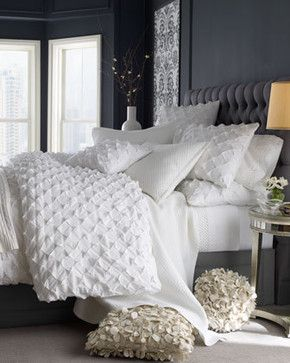 Different textures of the bedding and the pillows add warmth to the room. Rough but soft and cozy combined with smooth textures of the carpet, walls and furniture create balance in the room.