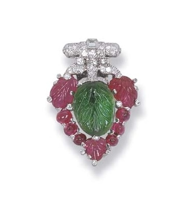 N ART DECO CLIP BROOCH, BY CARTIER   The carved emerald and ruby leaves to the diamond surmount, circa 1925, 3.2 cm. long, with French assay mark for platinum  Signed Cartier, no. 02667