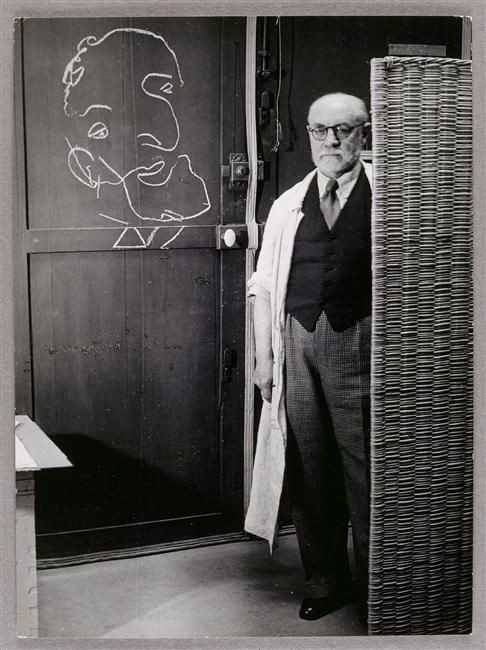 Brassaï, Henri Matisse standing against a screen and drawing with chalk, 1939