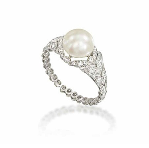 A BELLE EPOQUE NATURAL PEARL AND DIAMOND RING   Of foliate design, the bouton shaped natural pearl centre, to a millegrain-set old and single-cut diamond bezel and shoulders designed as a series of graduated laurel leaves, to the similarly-set diamond collet hoop, circa 1905, French marks for platinum