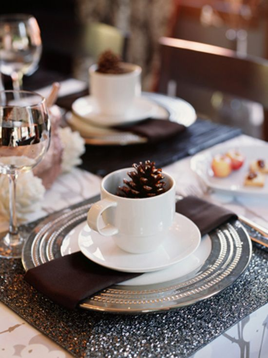 """Contrast Materials    A humble pinecone adds an organic touch to each place setting.  Tip: """"Have fun with materials; contrast ceramic with glass, wood and gleaming metal. Forgo the old standby tablecloth and opt for glamorous, polished silver chargers and chocolate-brown linen napkins."""""""