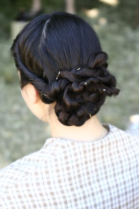 For thick hair, mid-back length:    1. Part hair in a Y part  2. Braid back section and wrap in a bun impossibly low on the nape of the neck.  Pin.  3. French roll the side hair and twist until it folds back on itself.  4. Pin this over the top of the bun, hiding the straggly hair ends  5. repeat for other side and lay the twist over the top of the first twist and pin.
