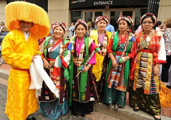 Wearing fabulous orange hat & traditional clothes Tibetan man & women in traditional dress, chubas, bright colors, pearls, coral, turquoise, white & green khatas, Happy Birthday to His Holiness the Dalai Lama, Tibetans at Kalachakra, Washington D.C., USA