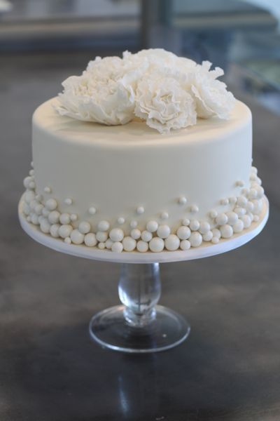 Simple one tier white wedding cake with pearls and flowers. Perfect for a very small reception