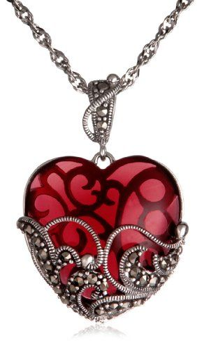 Project an air of mystery and allure with this captivating glass heart pendant. The gemstone-hued glass heart is held in an ornate sterling silver...