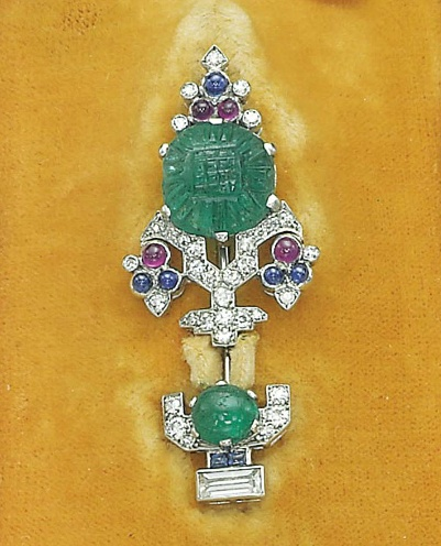 AN ART DECO 'TUTTI-FRUTTI' PIN, BY CARTIER   Designed as a stylized diamond-set tree centering upon a carved emerald, decorated with cabochon sapphire and ruby collets, to the cabochon emerald, sapphire and diamond opposite terminal, circa 1927, 4.6 cm, with French assay mark for platinum, in red leather fitted Cartier case  Signed Cartier, no. 8328