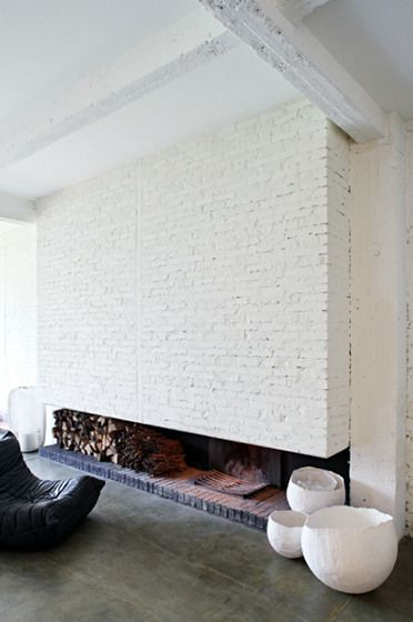 love this low fireplace and white brick walls