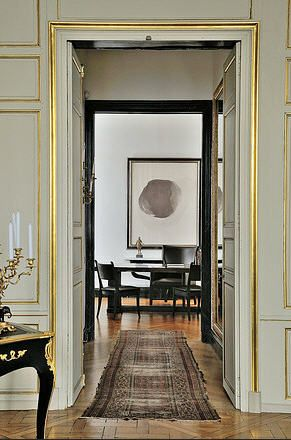Gold leaf on trim, modern art in the background, vintage rug. Elegantly worn and contemporary at the same time. Designer: Christian Liaigre.