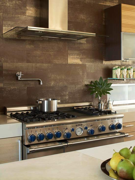 Rustic Appeal: Clad from counter to ceiling with durable chocolate-brown porcelain tiles, this backsplash harmonizes with the creamy-hue onyx and oak-veneer cabinetry in the kitchen. To impart the look of natural stone, the backsplash was edged with dark-gray grout.