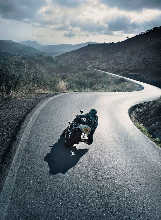 Motorbike rider on a twisting open road