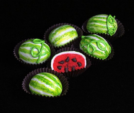 "Watermelon Cake Balls - From maker: ""Vanilla cake colored and flavored slightly with food extract. Frosting, form, dip in candy melts ...first white then green and paint the outside with coloring again. Mini chocolate chips for the seeds after I cut them. :)"""