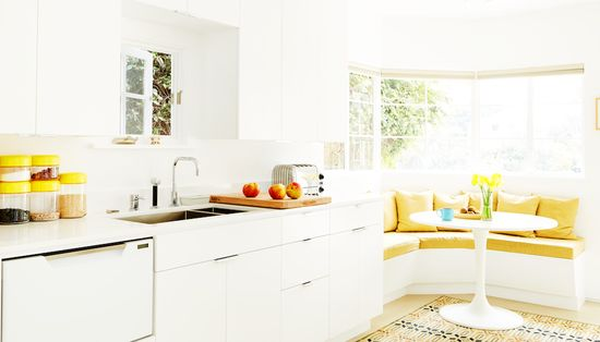 white and yellow modern kitchen with banquette seating // kitchen design
