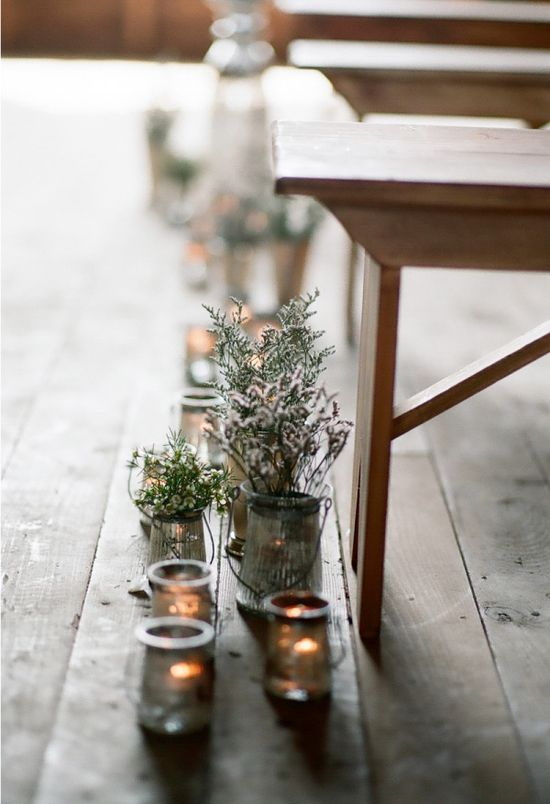 collection of jars and votive candles line this ceremony aisle