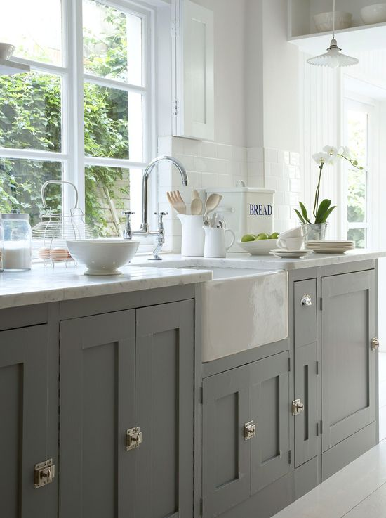 Grey painted cabinets with contrasting white marble worktops. We definitely advocate running window sills down to worktop level where possible to allow all available light to flood across the work-surface. Also note the prismatic glass pendant. Great look in the kitchen.