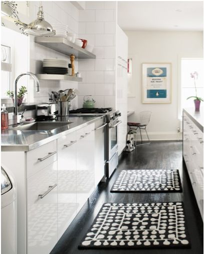 Open shelving, white cabinets and a punchy rug lighten up a small galley kitchen