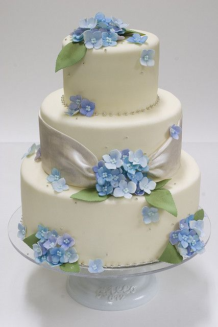 I like the ribbon detail on the middle tier. Blue Hydrangea Wedding Cake by studiocake, via Flickr