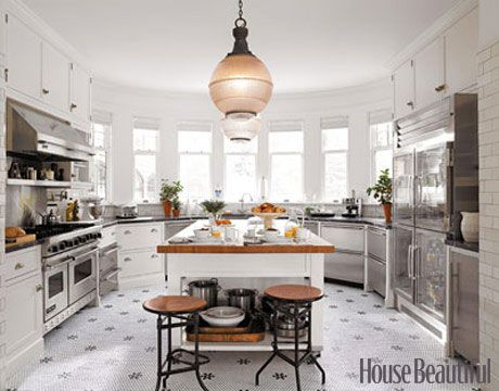 Twin 19th-century light fixtures in an elegant kitchen by designer Joan Schindler.