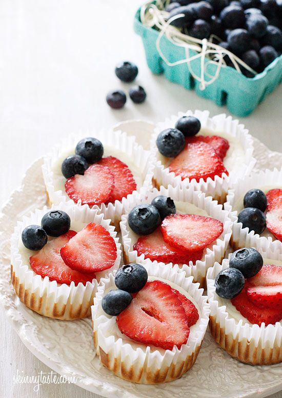 Mini cheesecake cupcakes made with Greek yogurt and cream cheese with a vanilla wafer crust topped with strawberries and blueberries.