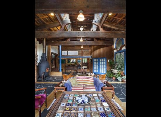 "Spanning the 31-foot width of Rajan's living room are a series of 8"" x 18"" fir beams salvaged from a decommissioned railway trestle in Eureka, California. The wood-burning stove was originally an ocean buoy picked up from the Oakland naval supply yard for $5."