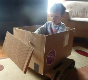 Cardboard Box Bulldozer by erinbrambilia: Made out of a cardboard box, a paper towel tube (you can't really see it, it's attached to the pusher on the front and inserted through a slot in the box so my son can push it forward like a real bulldozer), two cardboard tubes, corrugated paper, tape! #DIY #Toys #Bulldozer #Upcycle
